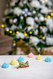Gingerbread sleigh and meringue on the table in front of defocused lights of Christmas decorated fir tree. Holiday sweets. New Yea stock images