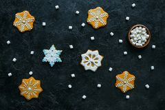 Gingerbread snowflakes and marshmallows. Top view of homemade christmas gingerbread snowflakes and marshmallows on black tabletop Royalty Free Stock Image