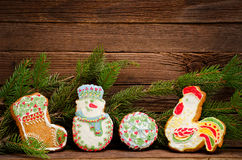 Gingerbread: sock, snowman, ball and cock, spruce branch on the background of wooden wall Royalty Free Stock Photos