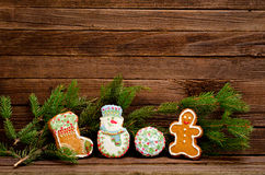Gingerbread: sock, snowman, ball and cock, spruce branch on a background of a wooden wall Stock Photos
