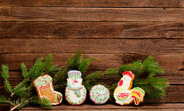 Gingerbread: sock, snowman, ball and cock, spruce branch on a background of a wooden wall with space for text Royalty Free Stock Image