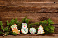 Gingerbread: sock, snowman, ball and fir-tree, spruce branch on a background of a wooden wall Stock Photography