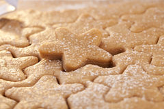 Gingerbread  star cookie cuts dough Royalty Free Stock Photos