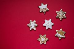 Gingerbread stars with white icing and sprinkles on red background Royalty Free Stock Photography