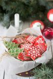 Gingerbread in a tin box in the background with Christmas toys, a candle and fir branches. royalty free stock images