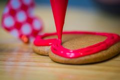 Valentines day gingerbread with dressing. Gingerbread valentines day cake dressing making with heart in the backround Royalty Free Stock Image
