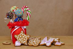 Gingerbread and vase with sweets. Sweets and gingerbread on a wooden table. Background in polka dots Stock Photo