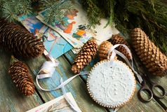 Free Gingerbread With A Picture Of A Snowman, Fir Cones, Branches And Postcards On A Wooden Background. Christmas Decor. Royalty Free Stock Photo - 103615605