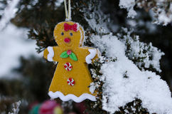 Gingerbread Woman Decoration on a Snowy Outdoor Christmas Tree Royalty Free Stock Images