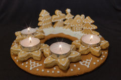 Gingerbread wreath and candles. Gingerbread wreath and lit candles on a dark background Stock Photos
