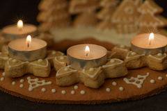 Gingerbread wreath detail. Gingerbread wreath and lit candles on a dark background Royalty Free Stock Images