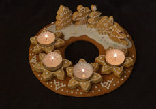 Gingerbread wreath upper view. Gingerbread wreath and lit candles on a dark background Stock Photos
