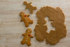 Gingerbreads and dough on wooden table. Close-up of gingerbreads and dough on wooden table Royalty Free Stock Photo