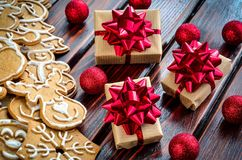 Creative Christmas decoration. Gingerbreads, gifts and baubles on a wooden background royalty free stock photo