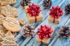 Creative Christmas decoration. Gingerbreads, gifts and cones on a wooden background stock images
