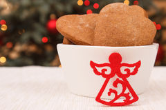 Gingerbreads in white bowl and christmas tree with lights in background Royalty Free Stock Images