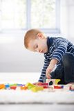 Gingerish boy playing with cubes Stock Photos