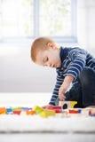 Gingerish boy playing with cubes. Gingerish little boy playing with building cubes at home on floor Stock Photos