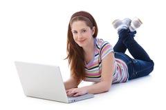 Gingerish girl using internet smiling. Young gingerish girl laying on floor, using laptop, browsing internet, smiling Royalty Free Stock Image