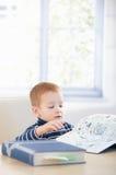 Gingerish kid studying cyclopaedia at home. Sitting at table Stock Images