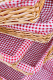 Gingham baskets. Pile of straw baskets lined by gingham cloths Stock Photos
