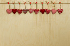 Gingham Love Valentine's hearts hanging on wooden texture backgr. Gingham Love Valentine's hearts natural cord and red clips hanging on light plywood texture Royalty Free Stock Image