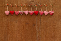 Gingham Love Valentine's hearts hanging on wooden texture backgr. Gingham Love Valentine's hearts natural cord and red clips hanging on rustic plywood texture Royalty Free Stock Photography