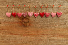 Gingham Love Valentine's hearts hanging on wooden texture backgr. Gingham Love Valentine's hearts natural cord and red clips hanging on rustic plywood texture Stock Photos