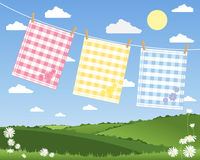 Gingham tea towels. An illustration of a washing line with three colorful gingham tea towels in a summer patchwork fields landscape under a blue sky Stock Photography