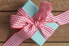 Gingham Wrapped Gift. Blue box wrapped in red gingham ribbon Royalty Free Stock Photos
