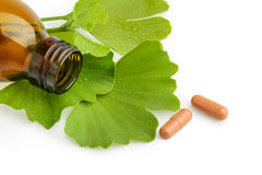 Ginkgo biloba leaves and medicine bottles with pills isolated Stock Photo