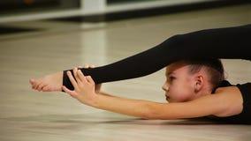 Ginnasta artistica sveglia del bambino femminile del primo piano in abiti sportivi neri fare riscaldamento in palestra ed eseguir