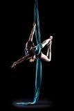 Ginnasta della giovane donna con le sete aeree relative alla ginnastica blu Fotografia Stock