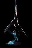 Ginnasta della giovane donna con le sete aeree relative alla ginnastica blu Fotografie Stock