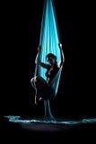 Ginnasta della giovane donna con le sete aeree relative alla ginnastica blu Fotografie Stock Libere da Diritti