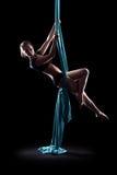 Ginnasta della giovane donna con le sete aeree relative alla ginnastica blu Immagini Stock Libere da Diritti
