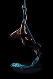 Ginnasta della giovane donna con le sete aeree relative alla ginnastica blu Immagine Stock