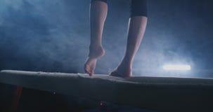 Ginnasta della ragazza che pratica su un fascio di equilibrio in palestra archivi video