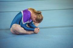 Ginnasta femminile che esegue allungando esercizio Fotografie Stock Libere da Diritti