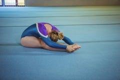Ginnasta femminile che esegue allungando esercizio Immagini Stock Libere da Diritti