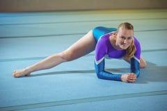 Ginnasta femminile che esegue allungando esercizio nella palestra Fotografie Stock