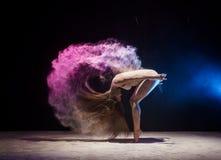 Ginnasta femminile graziosa in nuvola della polvere di colore Fotografie Stock Libere da Diritti