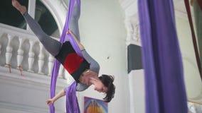 Ginnasta flessibile attraente dell'aria della donna che fa gli elementi acrobatici sulla seta aerea video d archivio