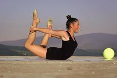 Ginnasta flessibile della donna della ginnasta in abiti sportivi neri con la palla verde Fotografia Stock