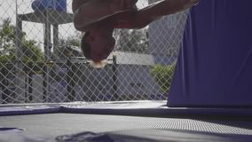 Ginnasta professionista che salta sul trampolino e che fa i trucchi al rallentatore stock footage