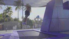 Ginnasta professionista che salta sul trampolino e che fa i trucchi al rallentatore video d archivio