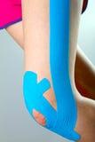 Ginocchio con nastro adesivo blu di kinesio immagine stock