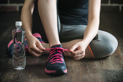 Ginocchio giù con il exerc di forma fisica dell'acqua della bevanda della stringa delle scarpe da tennis del legame immagine stock libera da diritti