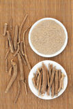Ginseng Herb. Ginseng ashwagandha herb root and korean powder over bamboo background Royalty Free Stock Photos