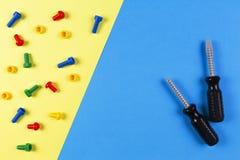 Gioca la priorità bassa La costruzione dei bambini gioca gli strumenti su fondo blu-chiaro e giallo Vista superiore Fotografia Stock